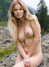 Stunning busty blonde posing naked in the mountains